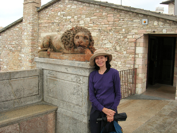 Wendy MacIntyre posed with stone lion sculpture in Assisi